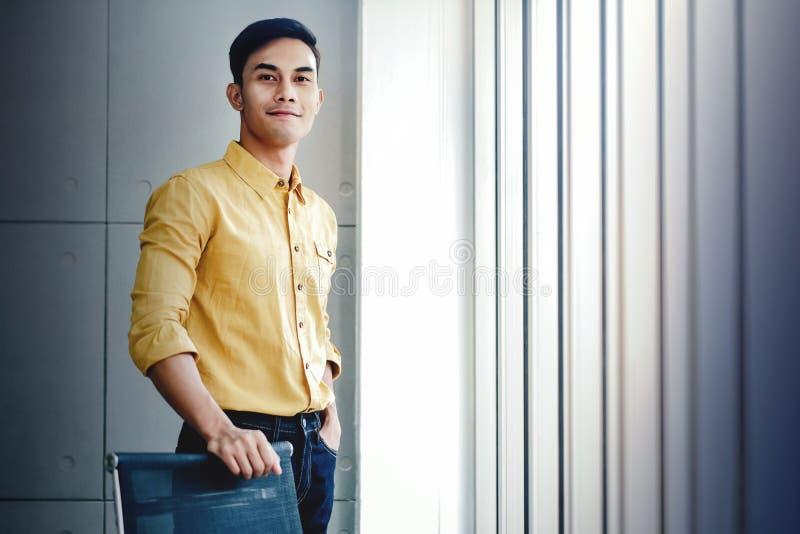 Ritratto di giovane uomo d'affari che fa una pausa la finestra in ufficio Esaminando macchina fotografica e sorridere Persona fel immagine stock libera da diritti