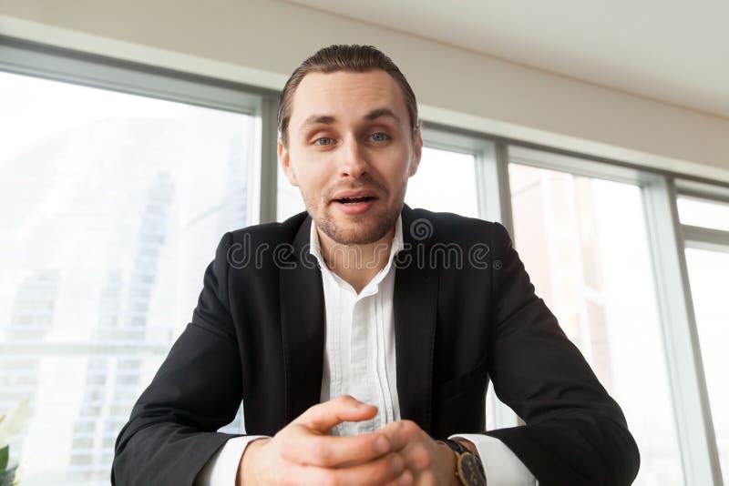 Ritratto di giovane uomo d'affari che guarda in camera e che parla immagine stock libera da diritti