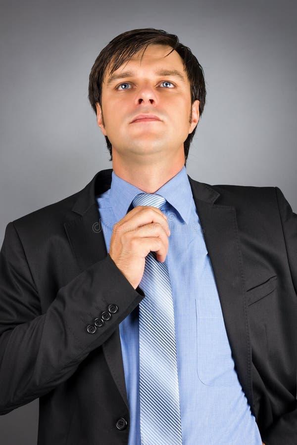 Ritratto di giovane uomo d'affari che regola il suo legame del collo che ottiene la r fotografia stock