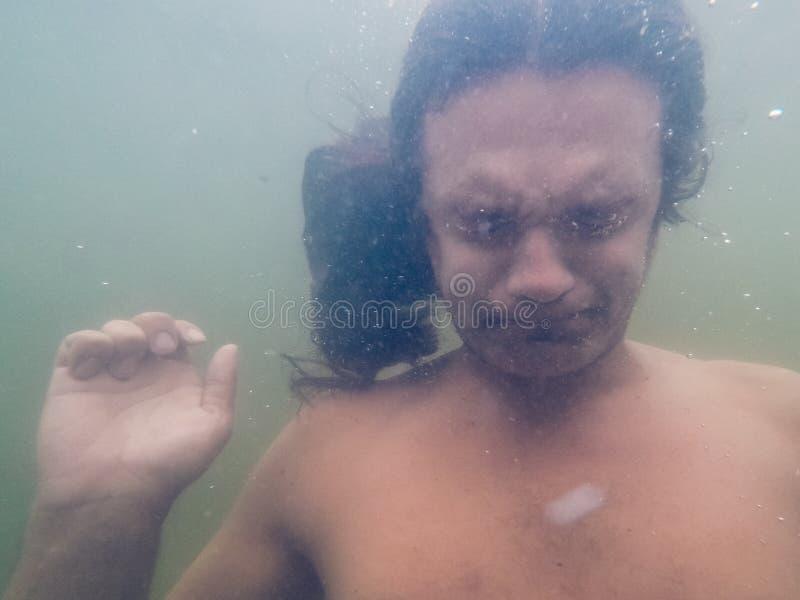 Ritratto di giovane uomo d'annegamento in acqua di mare, foto subacquea fotografia stock libera da diritti