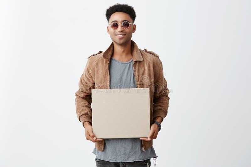 Ritratto di giovane uomo dalla carnagione scura bello con i capelli di afro in camicia grigia, rivestimento marrone ed occhiali d fotografia stock