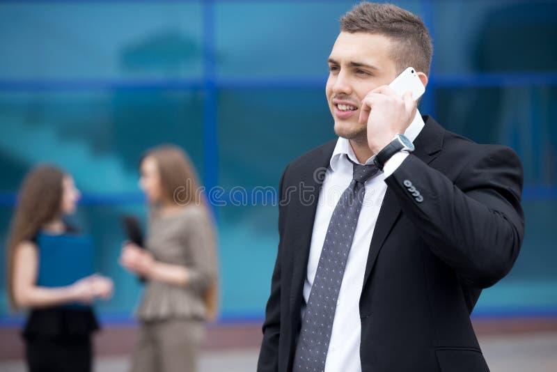 Ritratto di giovane uomo di affari che parla sul telefono all'aperto immagini stock libere da diritti