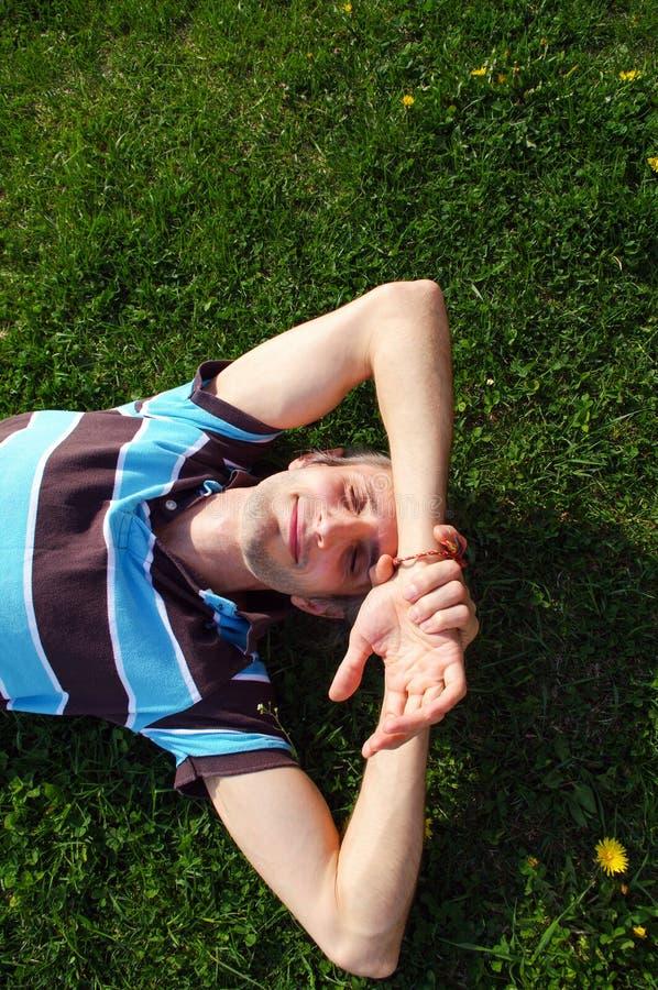 Ritratto di giovane uomo felice che si rilassa sull'erba con le sue mani nell'ambito della testa immagine stock libera da diritti