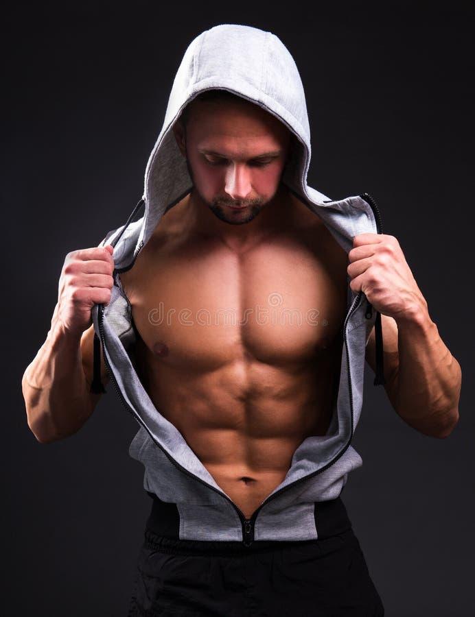 Ritratto di giovane uomo muscolare che mostra il suo torso sopra grey immagine stock