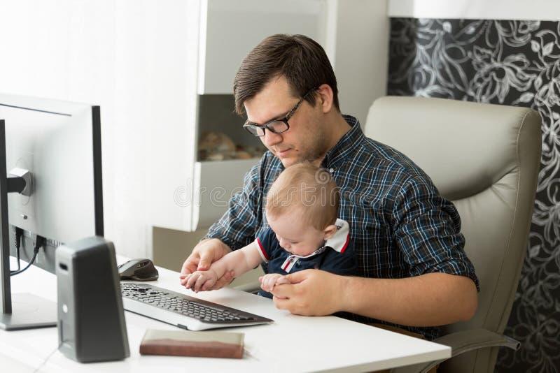 Ritratto di giovane uomo non retribuito che lavora a casa ufficio sul computer e che si occupa di suo figlio del bambino immagini stock libere da diritti
