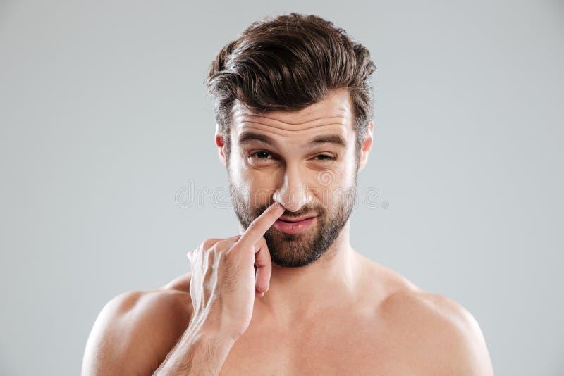 Ritratto di giovane uomo nudo barbuto che seleziona il suo naso immagine stock libera da diritti