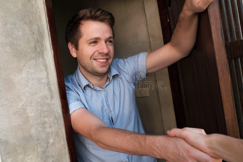 Ritratto di giovane uomo sorridente che apre la porta al suo amico e che lo accoglie favorevolmente che stringe mano immagine stock