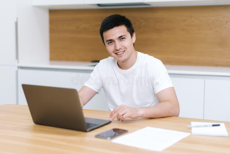 Ritratto di giovane uomo sorridente felice delle free lance che lavora a casa sul progetto immagine stock libera da diritti