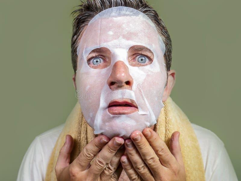 Ritratto di giovane uomo strano e divertente a casa che prova facendo uso della maschera facciale della carta di bellezza che pul fotografie stock libere da diritti
