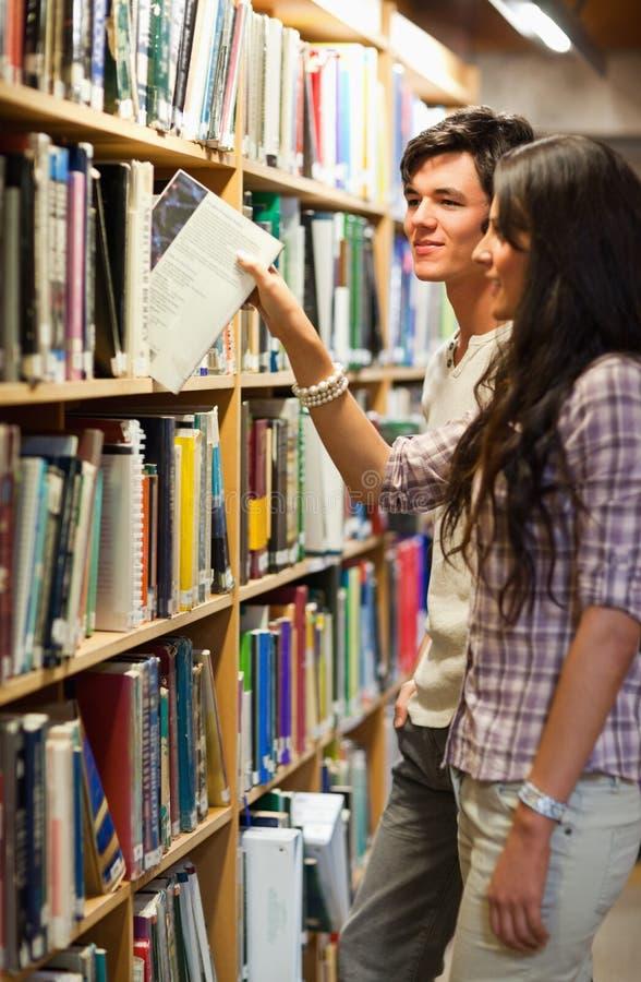 Ritratto Di Giovani Allievi Che Scelgono Un Libro Immagine Stock