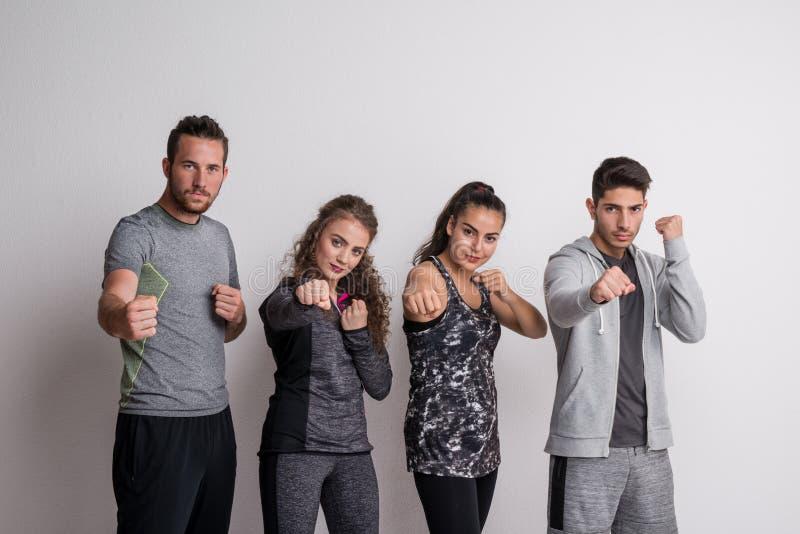 Ritratto di giovani amici allegri con la condizione degli abiti sportivi nella posizione di pugilato fotografie stock libere da diritti
