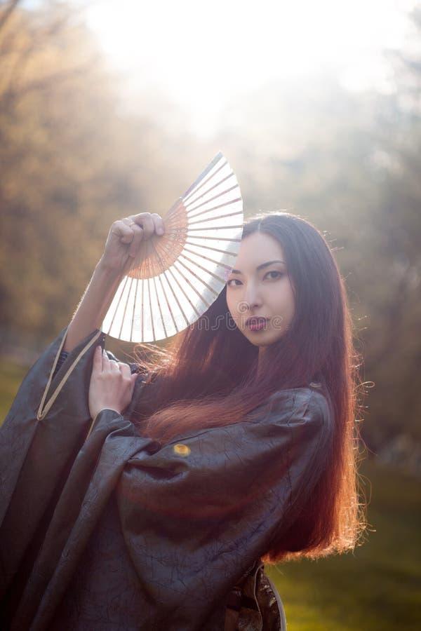 Ritratto di giovani bei asiatici in kimono grigio e con un fan immagine stock