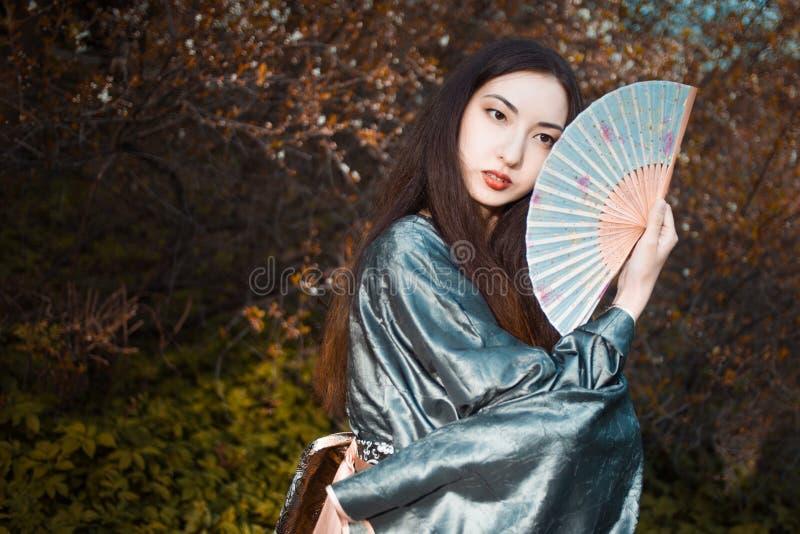 Ritratto di giovani bei asiatici in kimono grigio e con un fan immagini stock libere da diritti