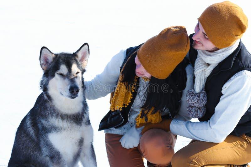 Ritratto di giovani coppie con i cani che sorridono e che abbracciano nell'inverno fotografia stock