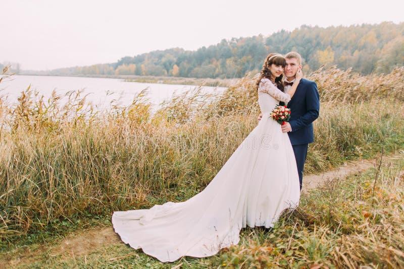 Ritratto di giovani coppie della bella persona appena sposata all'aperto Sposo felice che posa con la sua sposa sulla riva del fi fotografia stock libera da diritti