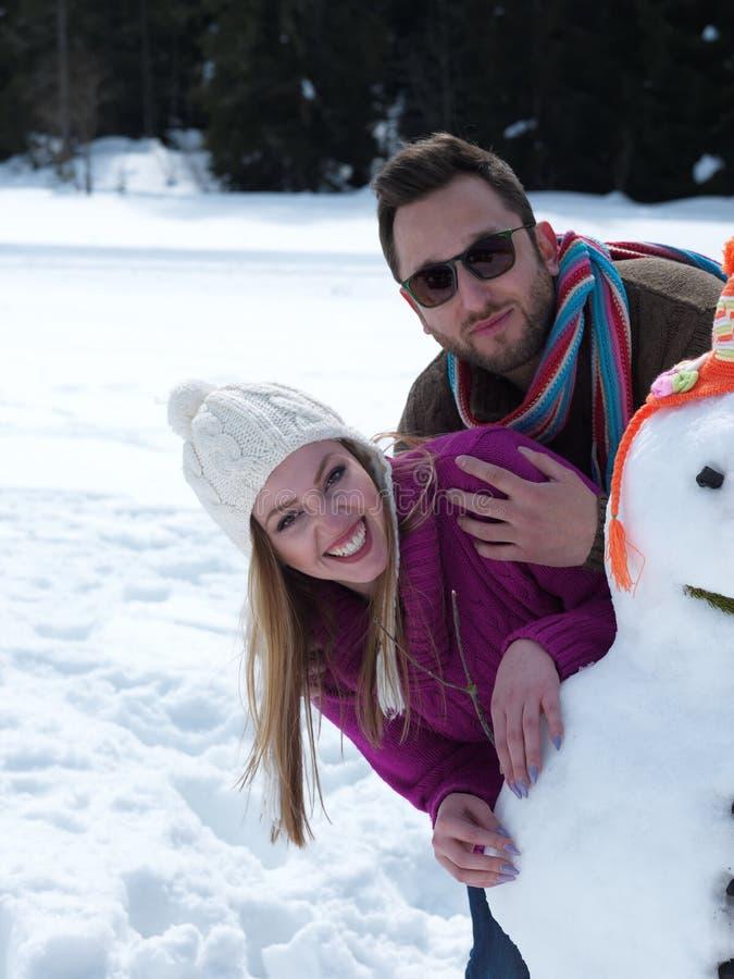 Ritratto di giovani coppie felici con il pupazzo di neve fotografia stock libera da diritti