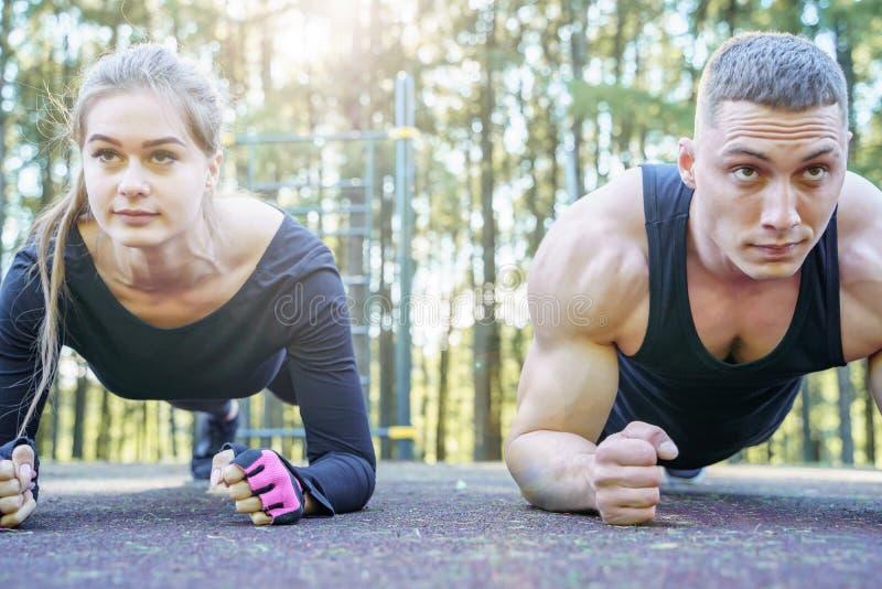 Ritratto di giovani coppie sportive che fanno l'esercizio della plancia all'aperto fotografia stock libera da diritti