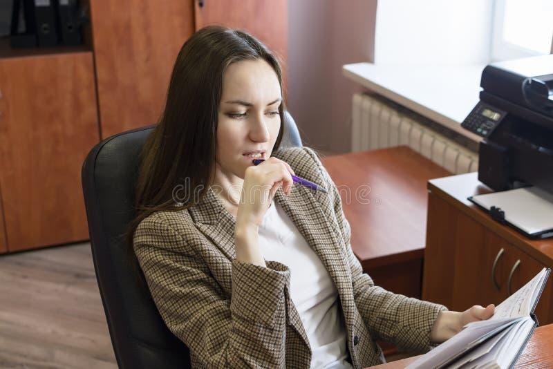 Ritratto di giovani donne di affari, pensando con la penna ed il blocco note in ufficio immagine stock