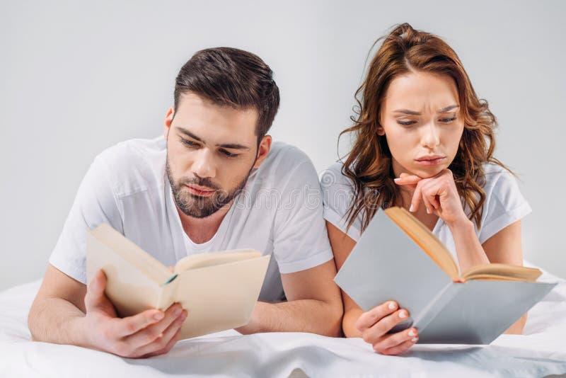 ritratto di giovani libri di lettura messi a fuoco delle coppie mentre trovandosi sul letto immagini stock