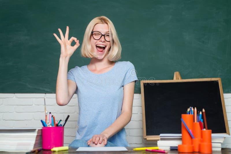 Ritratto di giovani strizzatina d'occhio dell'insegnante femminile ed APPROVAZIONE caucasiche divertenti di manifestazione Giovan immagine stock libera da diritti