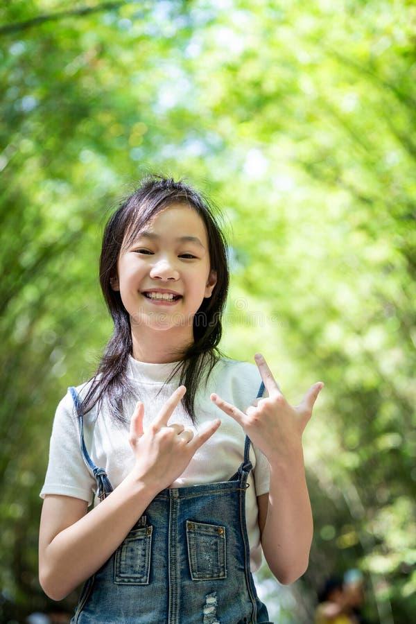 Ritratto di giusto significato sorridente di linguaggio dei segni della piccola ragazza asiatica ti amo ed esaminare la macchina  fotografia stock