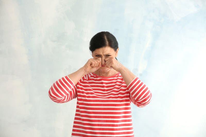 Ritratto di gridare donna matura su fondo leggero fotografie stock