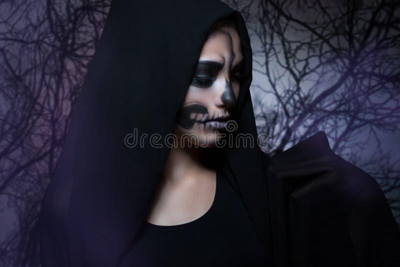 Ritratto di Halloween di giovane bella ragazza in un cappuccio nero immagini stock