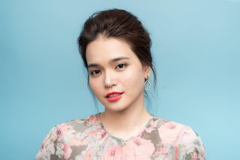 Ritratto di incantare la donna dell'Asia con il mazzo del fiore sopra fondo blu fotografia stock libera da diritti