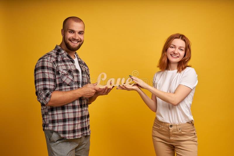 Ritratto di incantare uomo carismatico e donna che tengono una statuetta di legno dell'amore di parola Isolato sopra fondo giallo fotografia stock libera da diritti