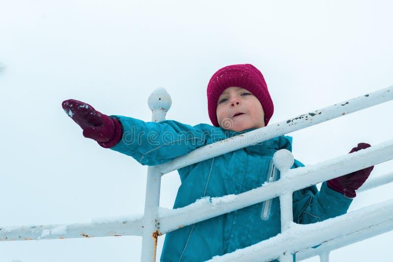 Ritratto di inverno del ragazzo nel cappello e nei guanti di Borgogna bambino emozionale che gioca e che ondeggia le sue armi fotografie stock libere da diritti