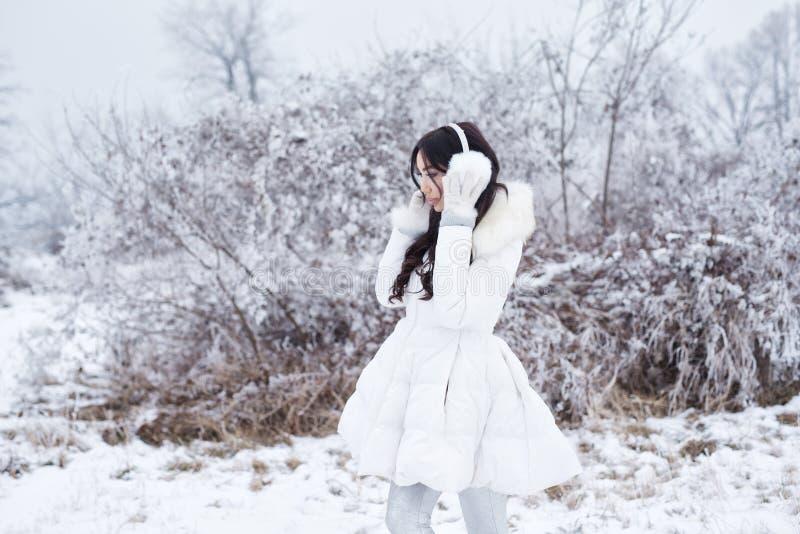 Ritratto di inverno dell'orecchio d'uso MU della giovane bella donna castana fotografia stock