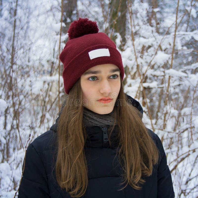 Ritratto di inverno della ragazza teenager nella foresta nevosa di inverno fotografie stock libere da diritti