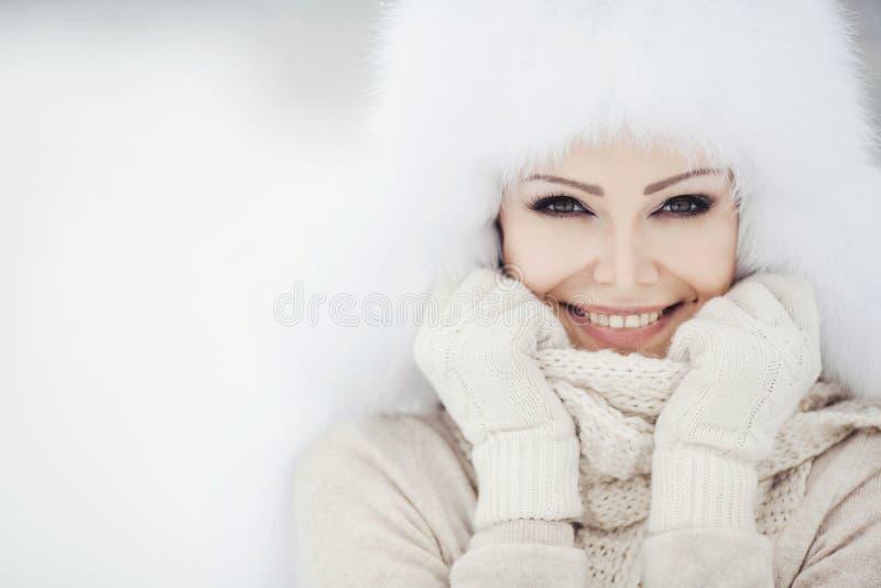 Ritratto di inverno di bella donna sorridente con i fiocchi di neve in pellicce bianche immagine stock