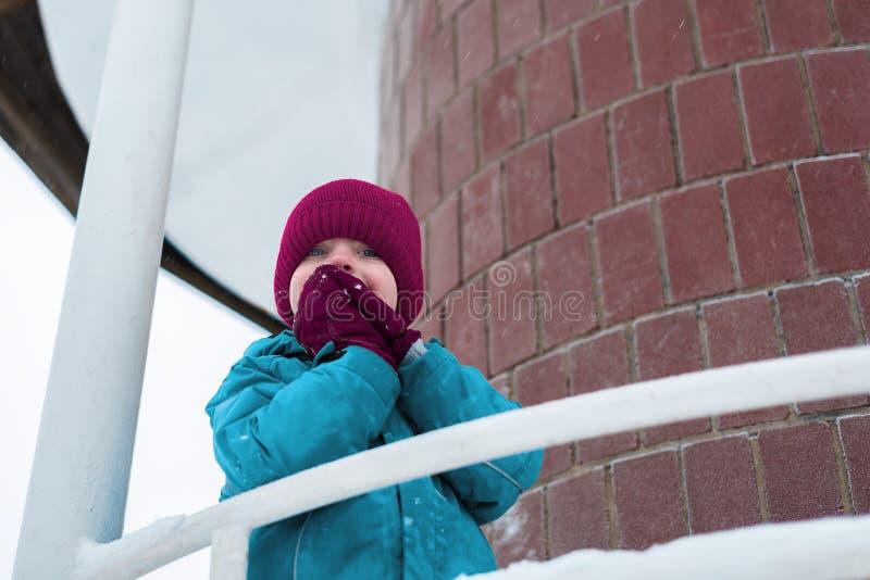 Ritratto di inverno di un ragazzo sveglio in cappello di Borgogna il bambino confuso ha coperto il suo fronte di sue mani fotografia stock libera da diritti