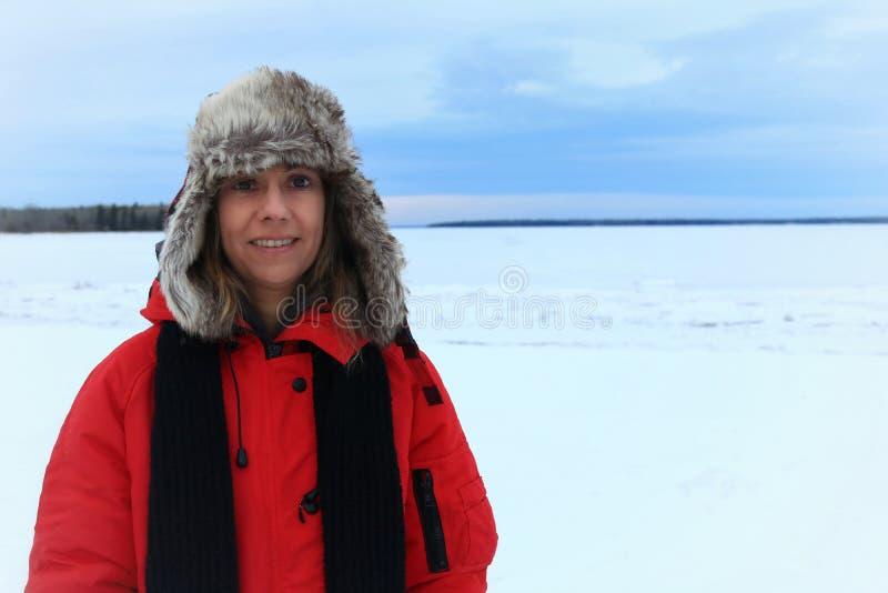 Ritratto di inverno di una donna che porta un cappello simile a pelliccia di aviazione e un rivestimento rosso immagine stock