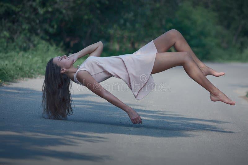 Ritratto di levitazione della giovane donna sulla strada fotografia stock