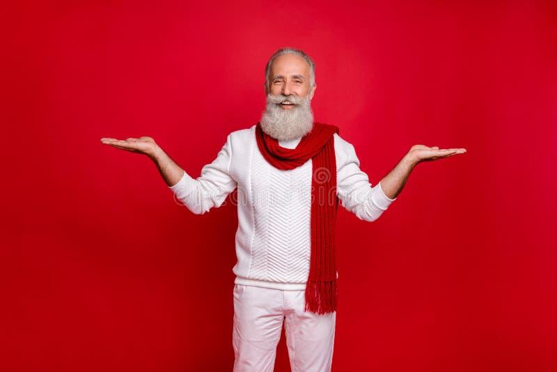 Ritratto di lui, un simpatico allegro e allegro uomo dai capelli grigi che regge lo spazio su due palme e un annuncio pubblicitar fotografie stock
