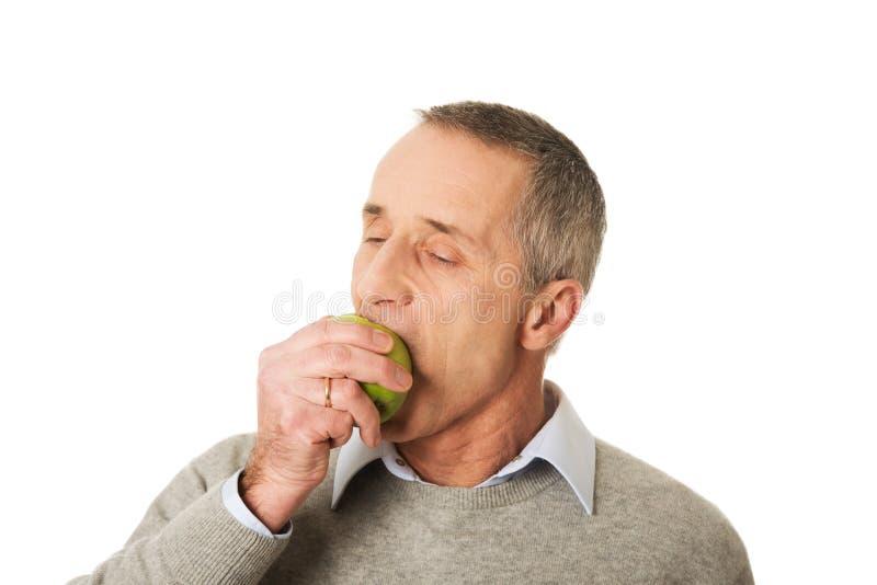 Ritratto di mangiatore di uomini maturo una mela immagine stock