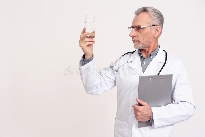 Ritratto di medico con lo stetoscopio e la lavagna per appunti che giudicano bicchiere d'acqua isolato fotografia stock libera da diritti
