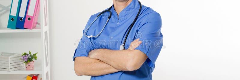 Ritratto di medico maschio felice allegro in ospedale con le mani attraversate Chirurgo con lo stetoscopio su fondo bianco medico fotografia stock libera da diritti