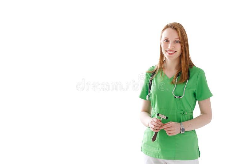 Ritratto di medico sorridente della donna con lo stetoscopio ed il martello in abito medico verde isolato su fondo bianco fotografia stock