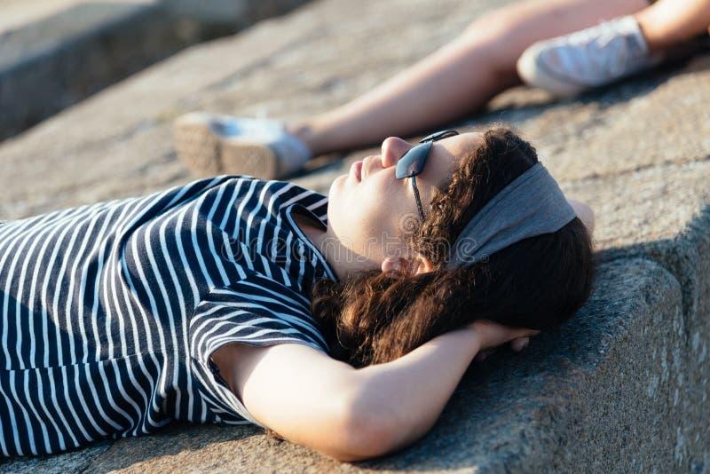 Ritratto di menzogne di rilassamento della bella ragazza sulle pareti che affrontano il sole immagine stock libera da diritti