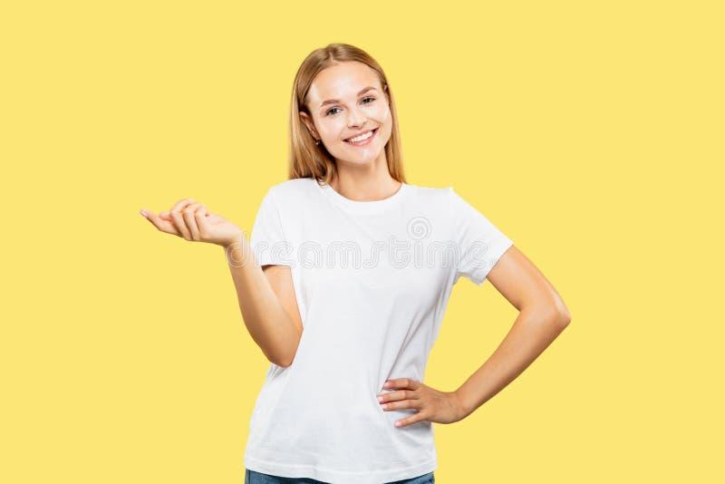 Ritratto di mezza lunghezza di una giovane donna caucasica sullo sfondo giallo fotografie stock libere da diritti