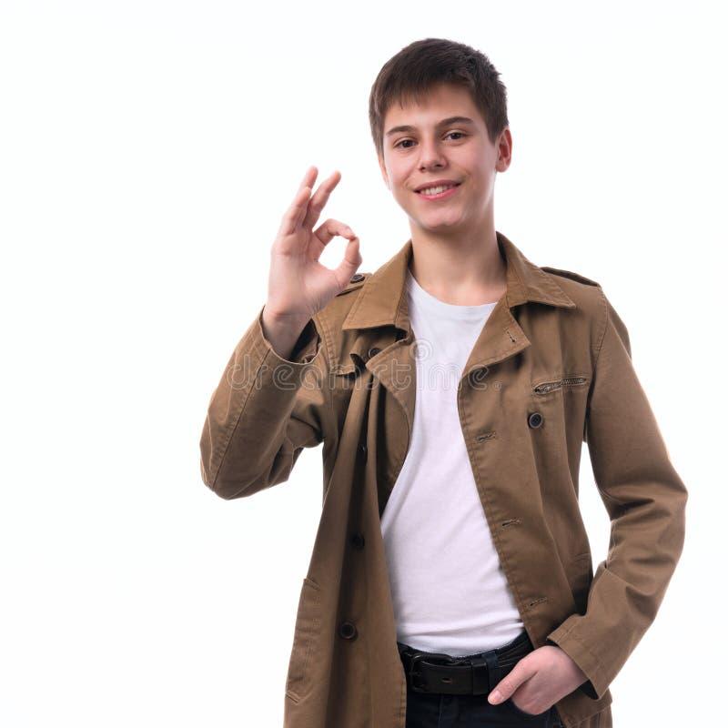 Ritratto di ritratto a mezzo busto di un ragazzo teenager grazioso sorridente che gesturing segno giusto su un fondo bianco fotografia stock