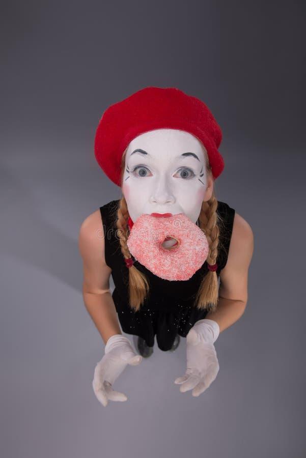 Ritratto di mimo abbastanza femminile che mangia un rosa saporito immagini stock libere da diritti