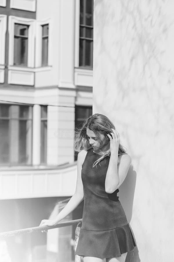 Ritratto di modo di bellezza Ragazza graziosa in vestito nero sul balcone fotografie stock