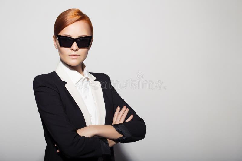 Ritratto di modo della donna seria vestito come agente segreto fotografie stock