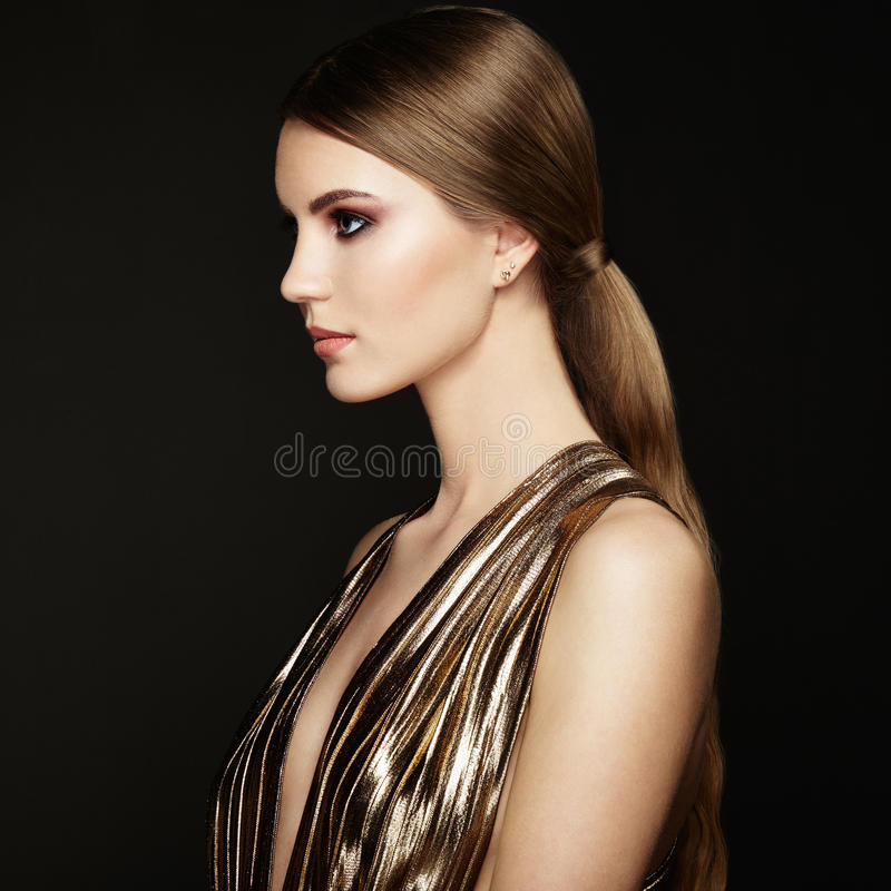 Ritratto di modo di giovane bella donna in vestito dall'oro immagini stock