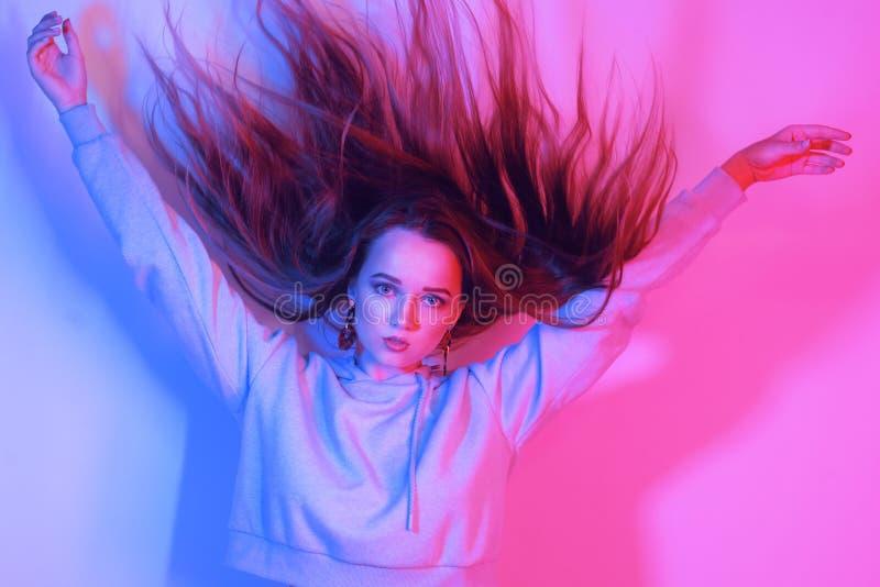 Ritratto di modo di giovane ragazza elegante Fondo al neon colorato, colpo dello studio Bella donna del Brunette Ragazza dei pant fotografia stock libera da diritti