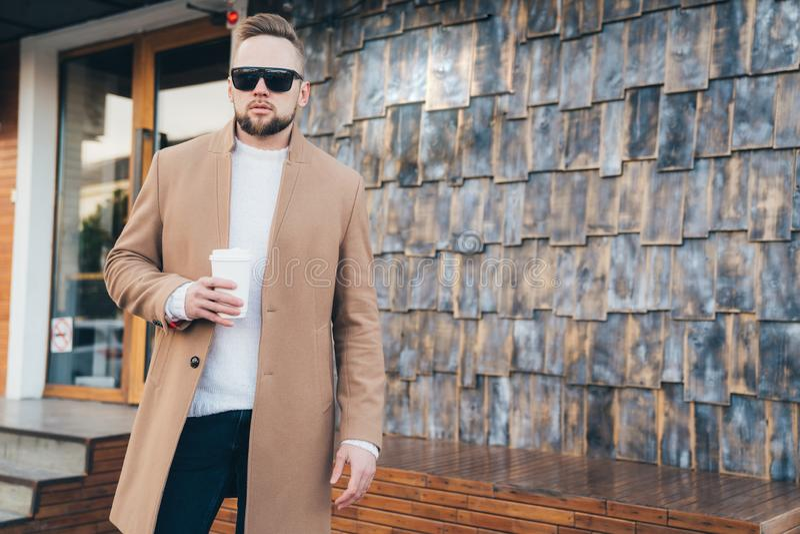 Ritratto di modo di stile di vita di giovane uomo europeo in cappotto e tazza di caffè beige, spazio della copia sulla parete di  fotografia stock libera da diritti